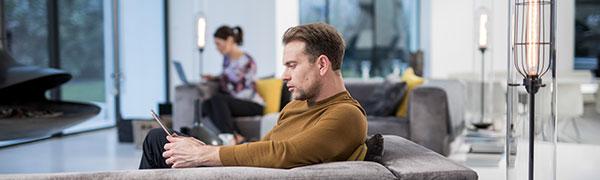 homem sentado em um sofá, trabalhando em um tablet