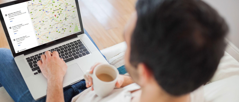 Homem com copo de café em uma mão e com laptop descansando nos joelhos