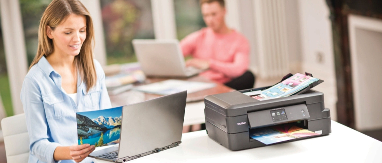 Mulher com laptop e impressora DCP-J785DW Irmão próximo