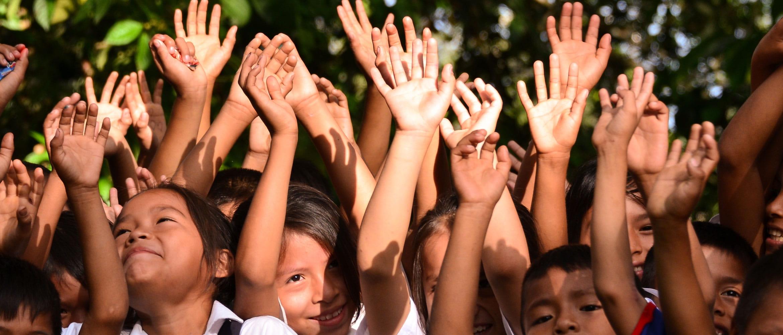 Grupo de crianças com as mãos para cima