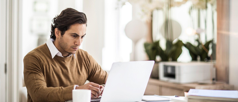 Homem com pulôver marrom usando laptop