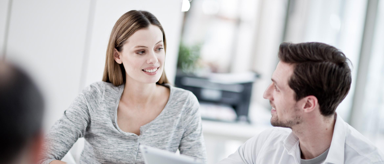Homem e mulher na frente do laptop estão sorrindo, impressora em segundo plano