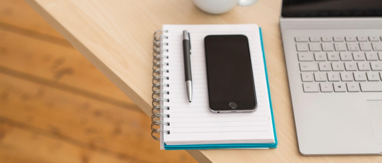 Telefone celular e caneta no notebook ao lado do teclado do laptop