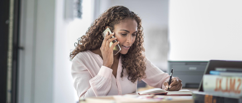 Mulher com cabelo encaracolado falando em um telefone celular