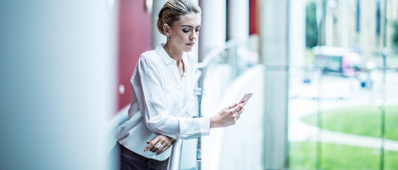 Mulher com blusa branca verificando seu celular