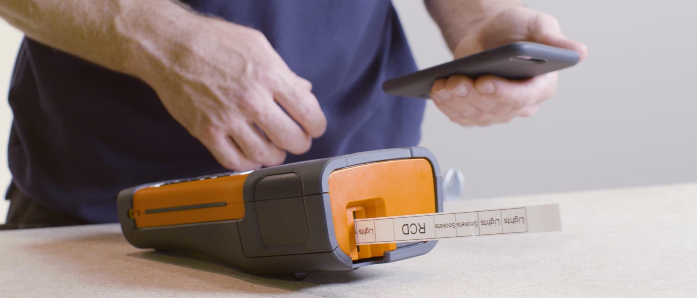 Homem com o celular em uma mão e impressora de etiquetas PT Brother