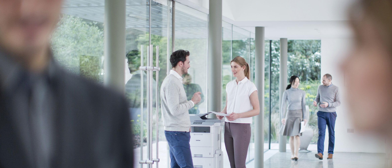Homem e mulher no meio do corredor ao lado da impressora Brother