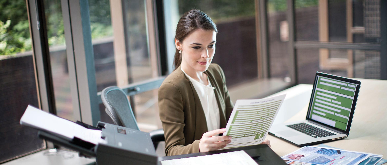 Mulher no escritório com laptop e scanner Brother