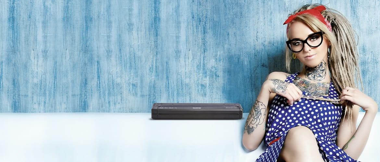 Homem com barba tatuada segurando uma impressora PJ portátil