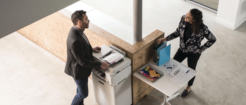 Escritório com 2 pessoas ao lado da impressora Brother