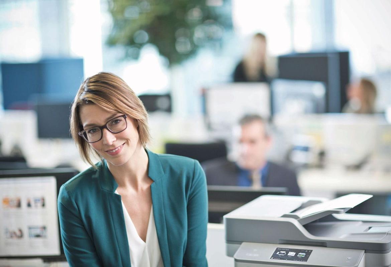 Mulher com óculos ao lado da impressora