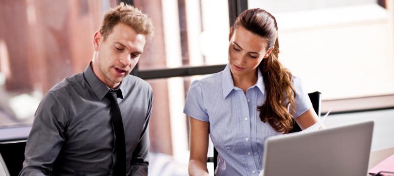 Duas pessoas na frente de um laptop