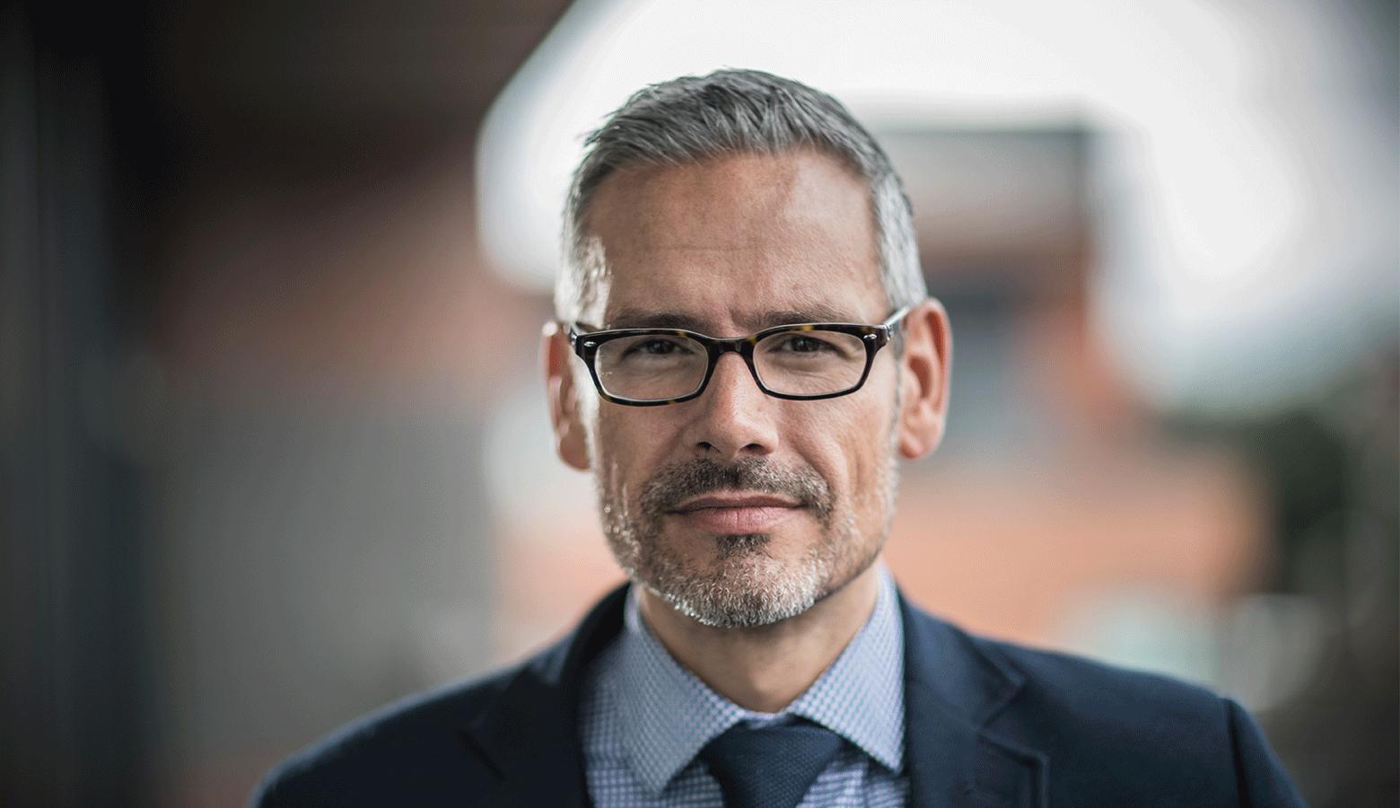 Homem grisalho com óculos