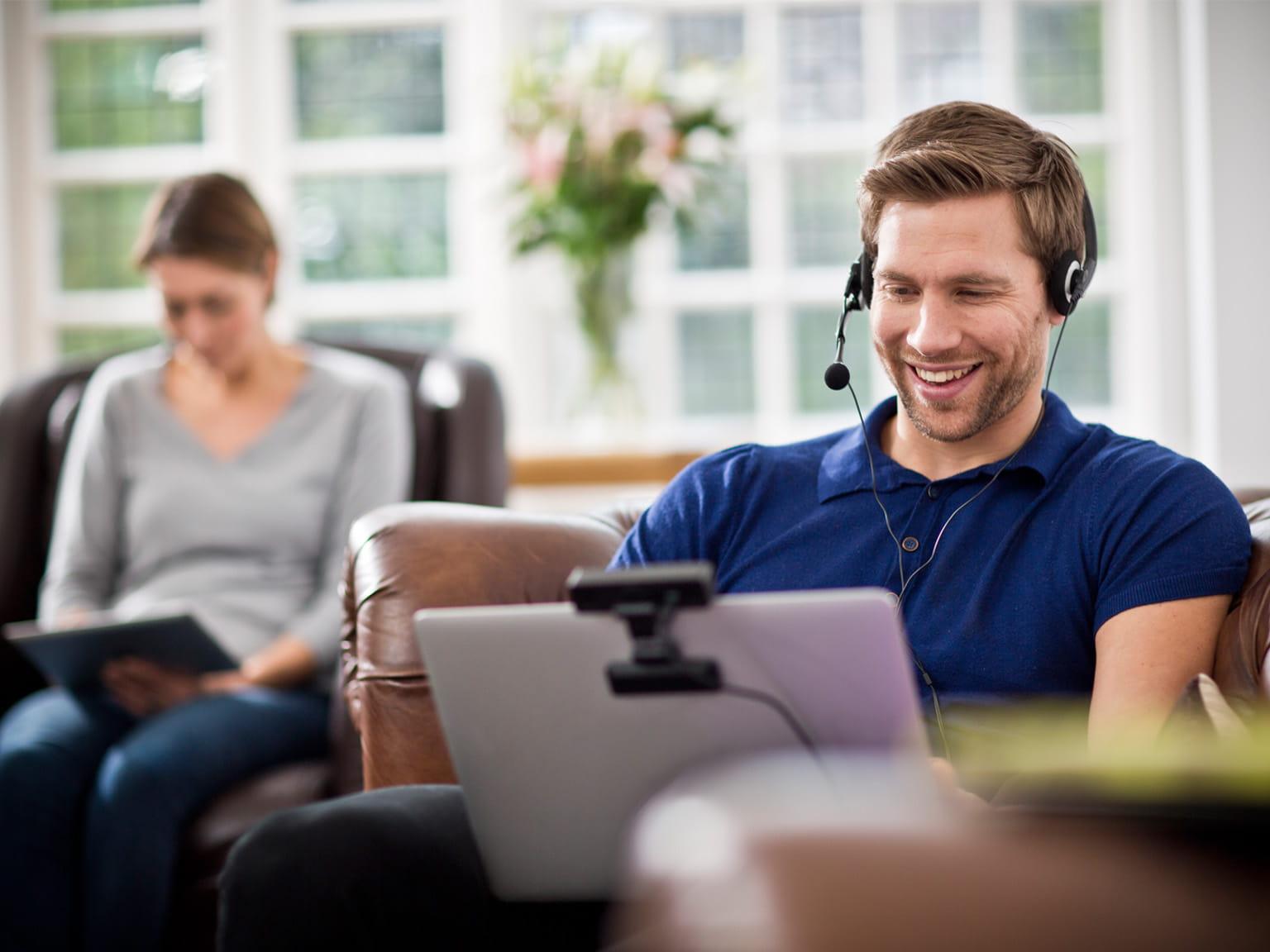 Homem con laptop falando por videoconferência