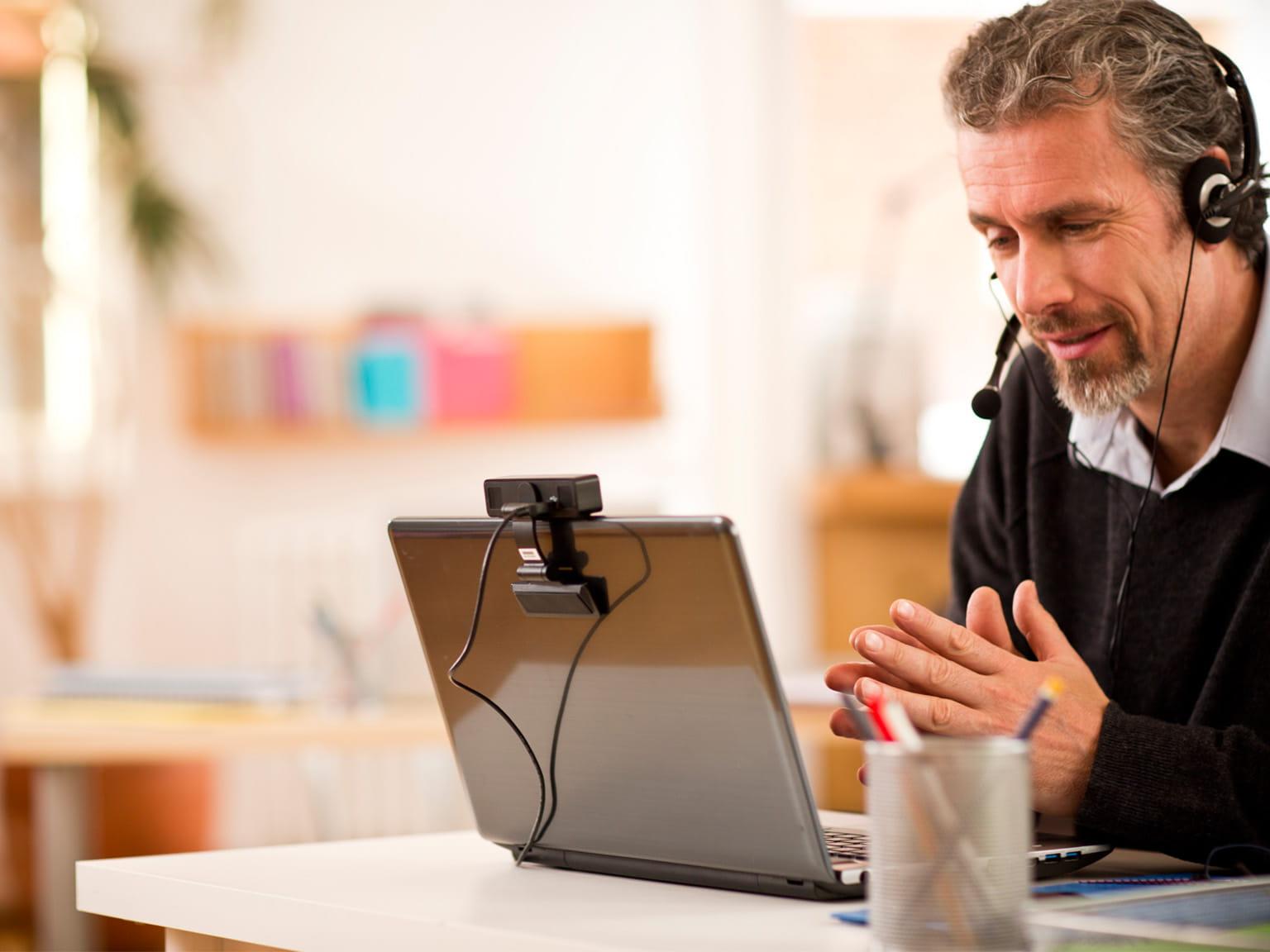 Homem con laptop e auscultadores