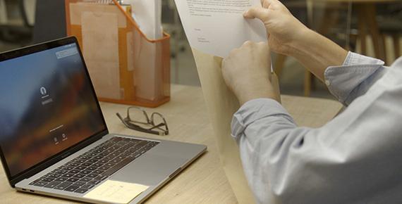 Mulher mantendo documentos ao lado do laptop